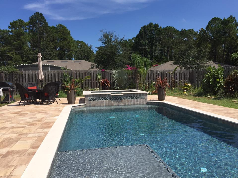 Custom pool design with sun shelf, raised spa, travertine coping, and large paver deck.